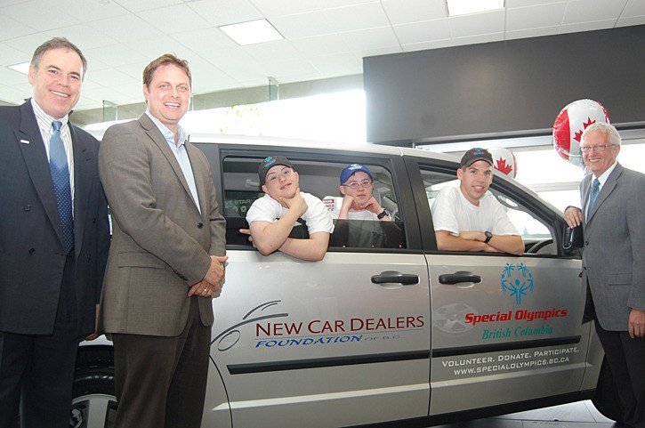 Paul McGeachie (left) and Mike Trotman presented the keys to a new 2011 Dodge Caravan to Special Olympics BC last week. Athletes Jaycob Low, Josh Low and Stuart Stevenson, and Dan Howe (far right), president and CEO of Special Olympics BC, accepted the vehicle at the Langley Chrysler Dodge dealership.
