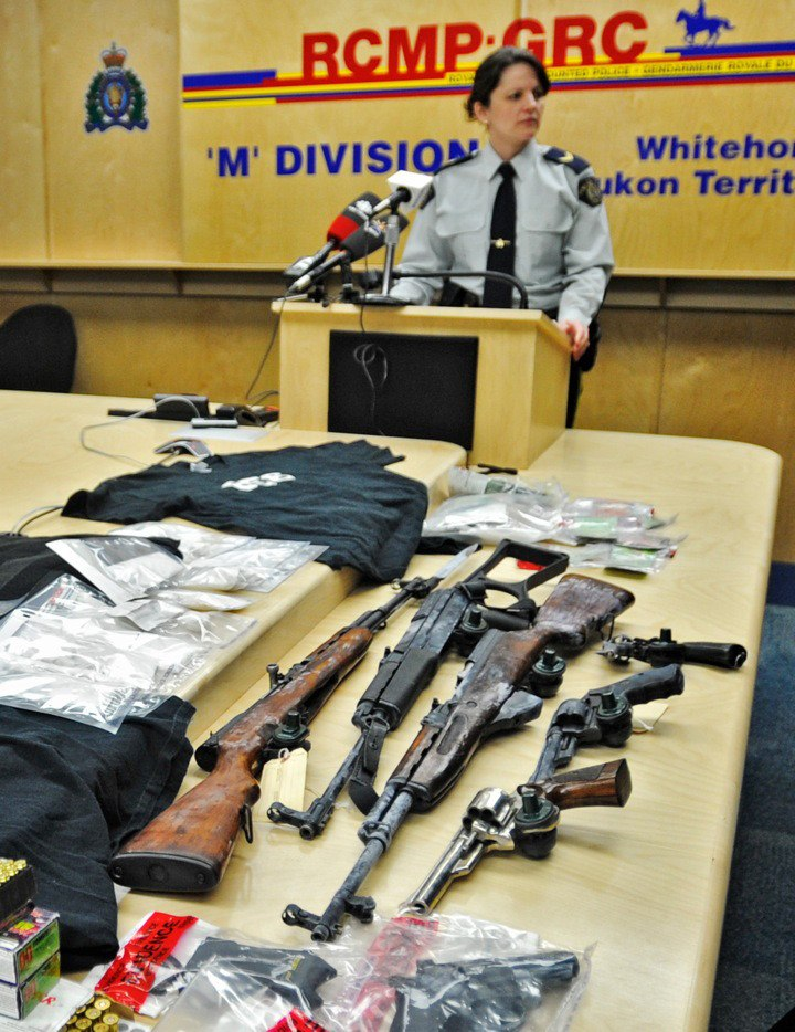 An RCMP officer in Whitehorse, Yukon, displays a collection of weapons, drugs and money that was seized during a March 16 raid in the territory's capital city. Police say the bust targeted members of the 856 gang, which has its roots in Aldergrove, but has expanded into northern B.C., Alberta, the Yukon and Northwest Territories over the past decade.