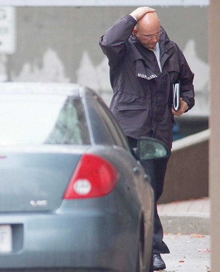 Cpl. Dale Carr of the Integrated Homicide Investigation Team outside of 9830 East Whalley Ring Rd. the day after six men were found dead. Several containers and bags of what appeared to be cocaine and crack were found in the suite where the victims men were executed in 2007.