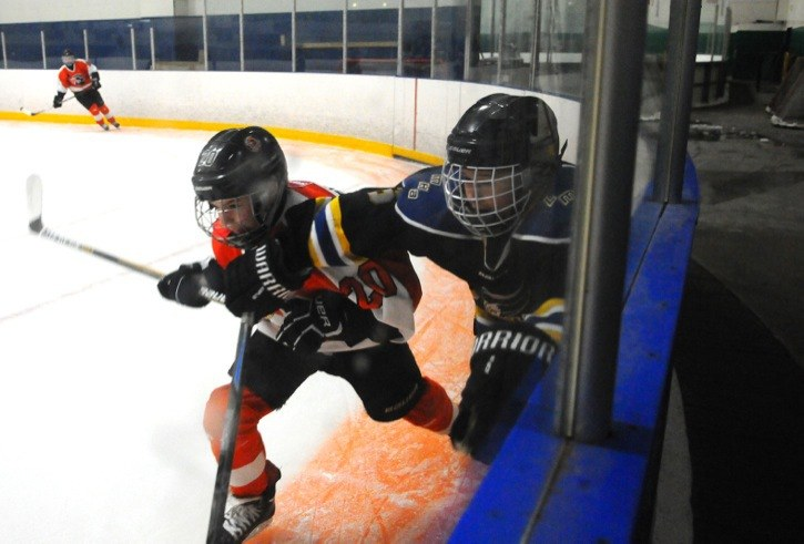 Langley A2 Eagles' Brad Fortin (right) and Semiahmoo Ravens' Conor Bryne chase the puck behind the goal during the Langley Minor Hockey Association Shatter the Glass bantam tier 2/3 hockey tournament at Sportsplex on Jan. 2.