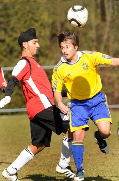 Langley United Chargers' Luke Sehved (right) clashes with a Delta Earthquake player during U17 soccer action at Topham Park on Sunday.