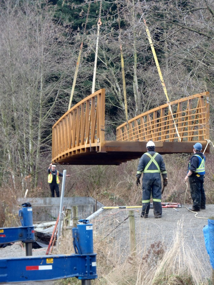 Township workers lower a bridge into place along the South Langley Regional Trail.
