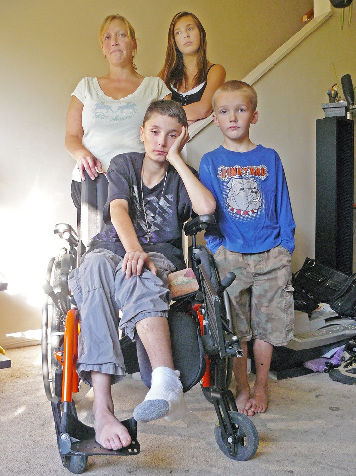Cheri Gilmour stands behind the wheelchair her son Demetri, 13, uses. Standing next to them are sister Leah, 13, and brother Dillin, 5 (brother Matthew, 10, was not home at the time). The family is facing eviction from their Langley townhouse.