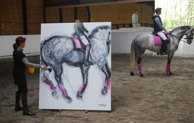 Langley artist Susan Falk, left, works on a large equestrian painting for her upcoming show at The Fort Gallery.