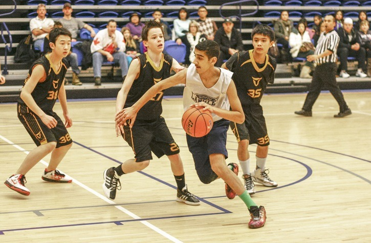 South Langley Titans' Arjun Samra dribbles past a pair of Balloholics opponents during the championship final of Basketball B.C.'s U13 Metro League playoffs at the Langley Events Centre Sunday morning. The Titans won 47-33.