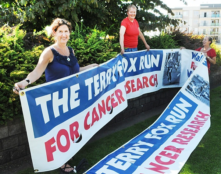 Terry Fox organizing committee members Rosemary Wallace (left) Renate Gueulett (centre) and Lilianne Fuller unfurled a new 36-foot long banner that will be strung across Fraser Highway at 208 Street on Sept. 4. The Terry Fox Run will begin and end at the Spirit Square in Douglas Park on Sunday, Sept. 16.