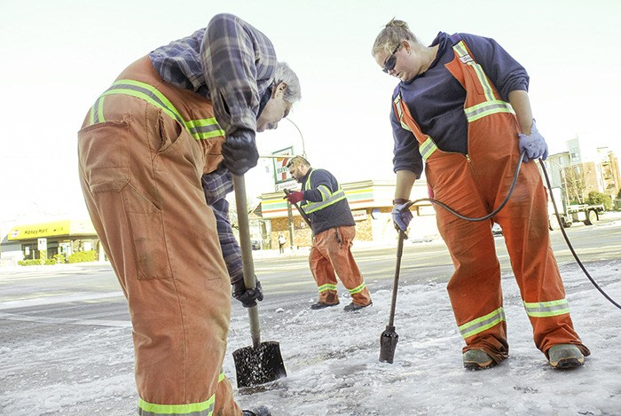 A Langley City crew clears ice and and snow from an intersection. From left: Bill Kerton Roberto Di Lorenzo and Sonia Custock, who is using a blowtorch to help break up the ice. The City spent nearly $180,000 to clear away snow and ice in December.