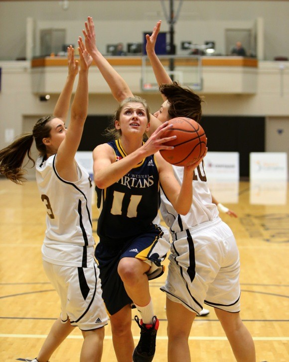 Trinity Western's Holly Strom splits a pair of Manitoba Bisons defenders on Nov. 24 at the Langley Events Centre. Strom scored 23 points in leading the Spartans to their first victory of the season.