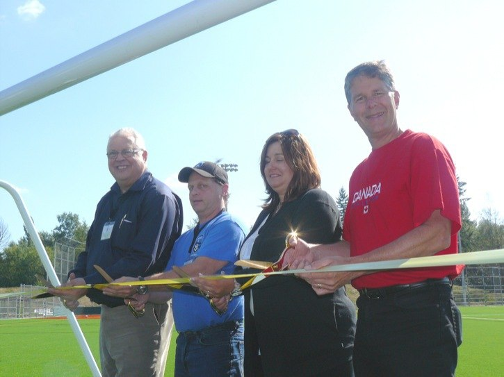 Left to right: Langley Township mayor Rick Green, Langley Football Club president Rory Wakelin, Langley United Youth Soccer Association president Betty Boucas and Langley MP Mark Warawa cut a ribbon to officially open the new artificial turf field at Willoughby Community Park.