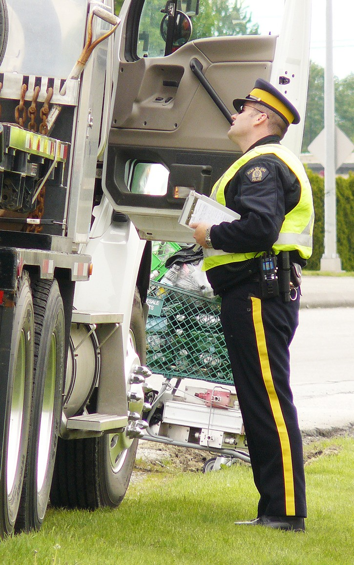 An RCMP officer tells a trucker why he's been pulled over. Officers conducted a safety blitz Wednesday morning at the intersection of Hwy. 10 and Fraser in Langley. Video online at www.langleytimes.com.