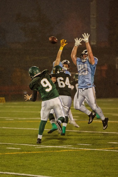 Langley Rams' Brock Gowanlock (#99) leaps to try and block the pass attempt of Valley Huskers' quarterback Noah Falconer on Saturday night in Chilliwack. The Rams won 56-7.
