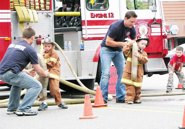 Langley City Firefighters help children put on turnout gear for the 2010 junior firefighter challenge.