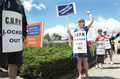 Locked out postal workers Kelly Kimber (left), Dan Messenger and Kelly Telford whistle and wave to motorists outside the Production Way postal facility in Langley City.  The lockout of employees, which began June 15, continues. Back-to-work legislation is now being debated in Ottawa.