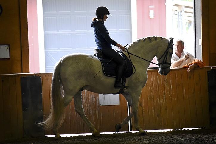 Tim Ansell watches with pride as his 18-year-old daughter, Hillary, rides past during a lesson at High Point Equestrian Centre on Wednesday. The Ansell family was visiting Langley from Kelowna after the Make-A-Wish Foundation granted them a surprise horse-themed package. In addition to the riding lesson, Hillary, who has cystic fibrosis, also received a shopping spree at Langley's The Dog & Pony Shop, a new saddle for her horse, and many other equine gifts.