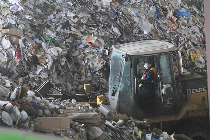 Piles of recyclables wait to be processed at Surrey's Material Recovery Facility, where single-stream recycling materials jumbled together in blue boxes are sorted out.