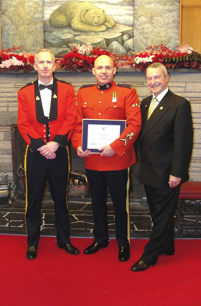 Cpl. Joel Glen, centre received an award of valour at a ceremony in Victoria last month after he successfully subdued a man who threw a butcher knife at him and brandished a cast iron frying pan. He was joined by Langley RCMP Supt. Derek Cooke (left) and City of Langley Mayor Peter Fassbender (right).