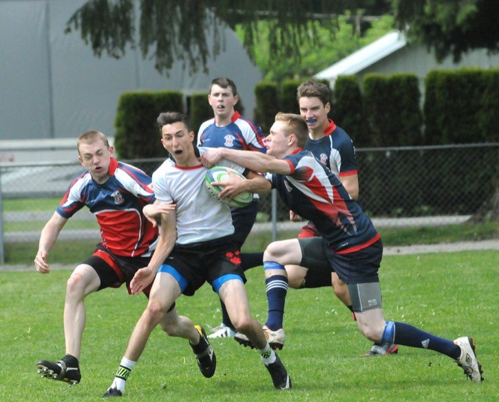 D.W. Poppy Secondary was a hub of activity last Friday afternoon as 15 teams — representing five schools — in five levels took to the pitch as part of a Rugby 7s tournament. Poppy's Logan Belansky tries to fend off Brookswood's Aiden Reese and Dylan Brewer in senior boys play.