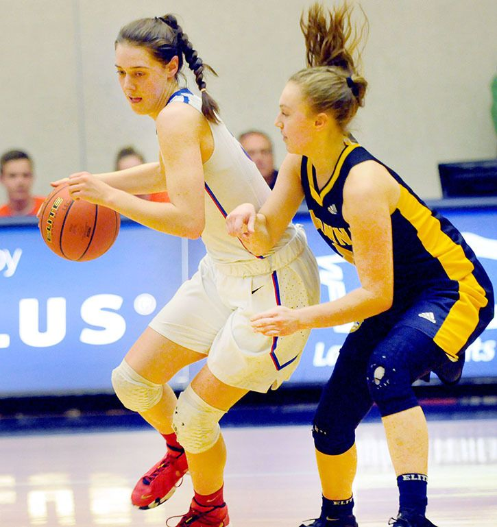 Brookswood Bobcats' Louise Forsyth (left) shields the ball from her Kelowna Owls opponent during quarter-final action at the B.C. AAA senior girls provincial championships at the Langley Events Centre.