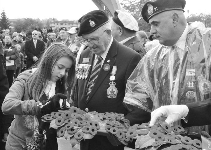 A Girl Guide selects a poppy from Royal Canadian Legion zone commander Walter Poustie, during the 2011 Remembrance Day service in Langley City.