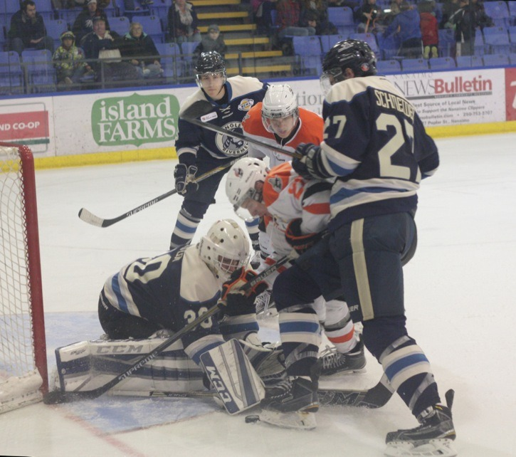 Langley Rivermen's Jordan Schneider delivers a cross-check to Nanaimo Clippers' Corey Renwick as Bo Didur tries to cover the puck. The Clippers defeated Langley 4-3 in BCHL action on Saturday night.