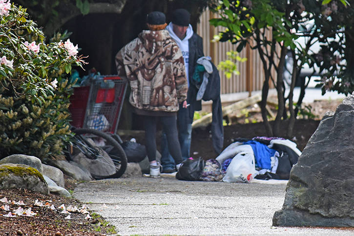 A man and women, accompanied by a full shopping cart, bike, and heap of garbage, on the corner of Eastleigh Crescent at a camp set up there last year. Langley has the dubious distinction of seeing the third highest increase in homeless in a new released report of Metro Vancouver communities.