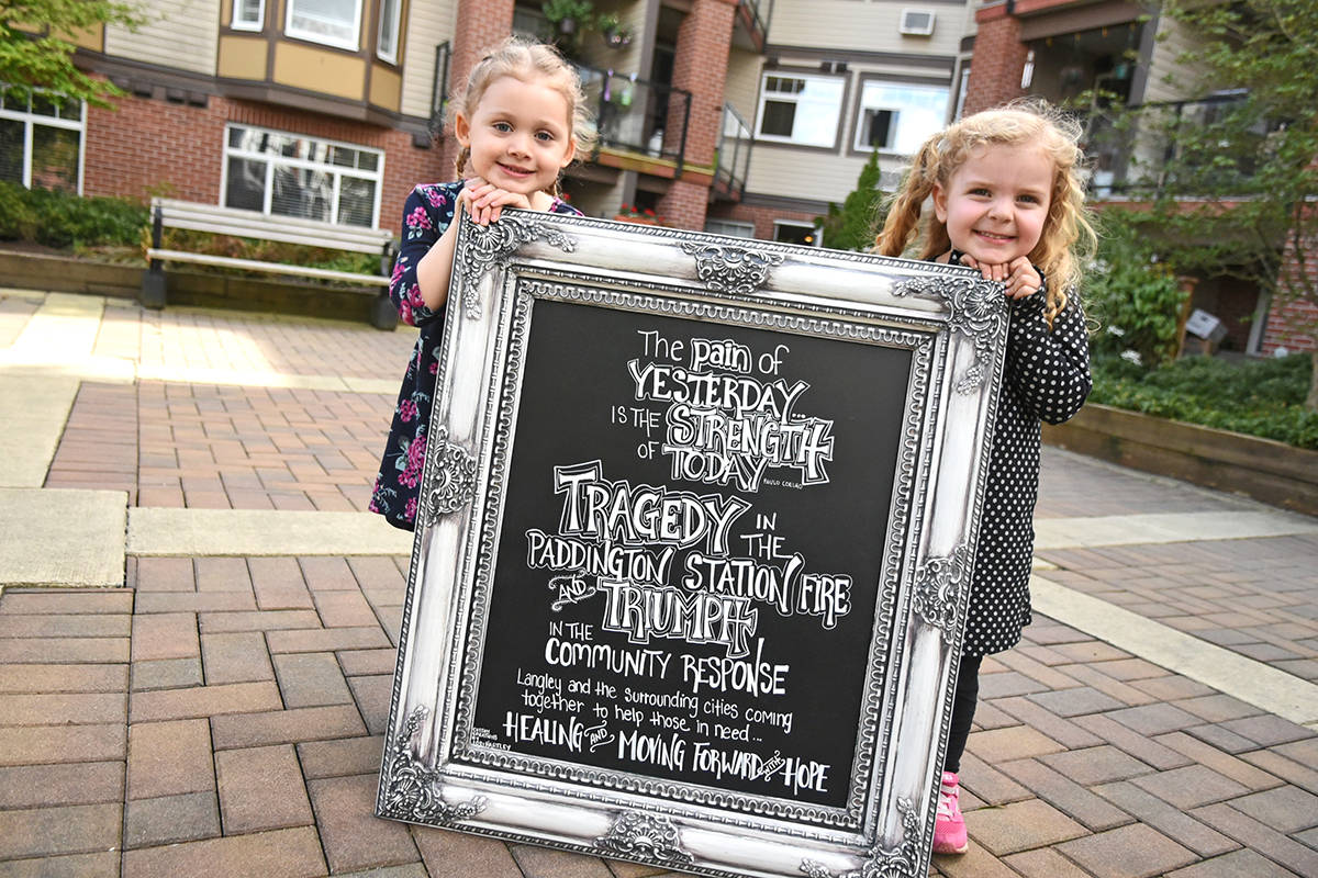 Paddington Station residents Peyton Adams, 3, and Khloe Newell, 3, hold up an artistic sign, created by Jodi Hartley in response to the December fire that ripped through the building. Peyton is the daughter of Emily Taylor Adams, a Langley musician who wrote a dedicated song about the disaster and performed it at Karen Lee Batten's concert fundraiser. That was the first time Adams had taken the stage in six years, and she is now relaunching her music career. In the last four months, a total of $250,000 has been raised by the community.                                Miranda Gathercole Langley Times