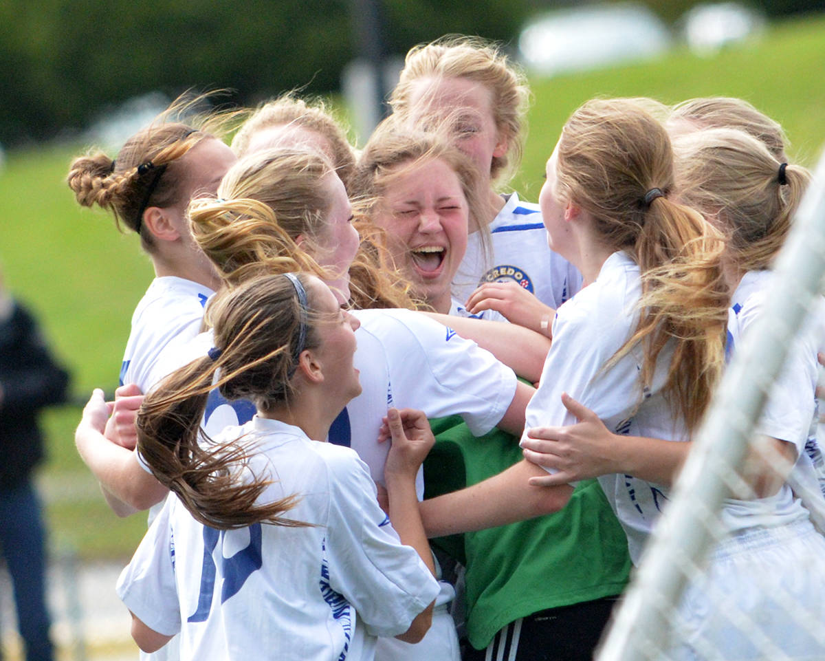The Credo Christian senior girls soccer team mob goaltender Sarah Slump (green) and celebrate after their penalty kick victory over Langley Christian in the Fraser Valley championship final on May 18.                                 Gary Ahuja Langley Times