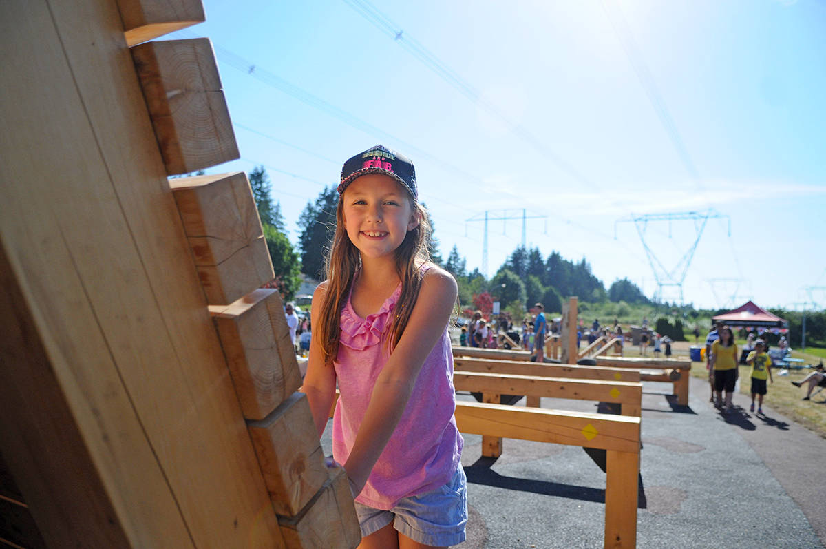 Langley City resident Lily Neufeld, 8, prepares to climb up on a piece of equipment during the grand opening of Penzer Park's new outdoor parkour facility. Miranda Gathercole Langley Times