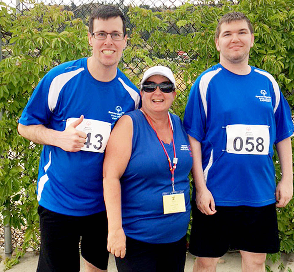At the Special Olympics BC Summer Games in Kamloops July 6 to 8, Langley athletes Christopher Lakusta (left) and Cole Trousil (right) medaled in three events each, both in track and field. They flanked coach Lynda McGaire. Submitted photo