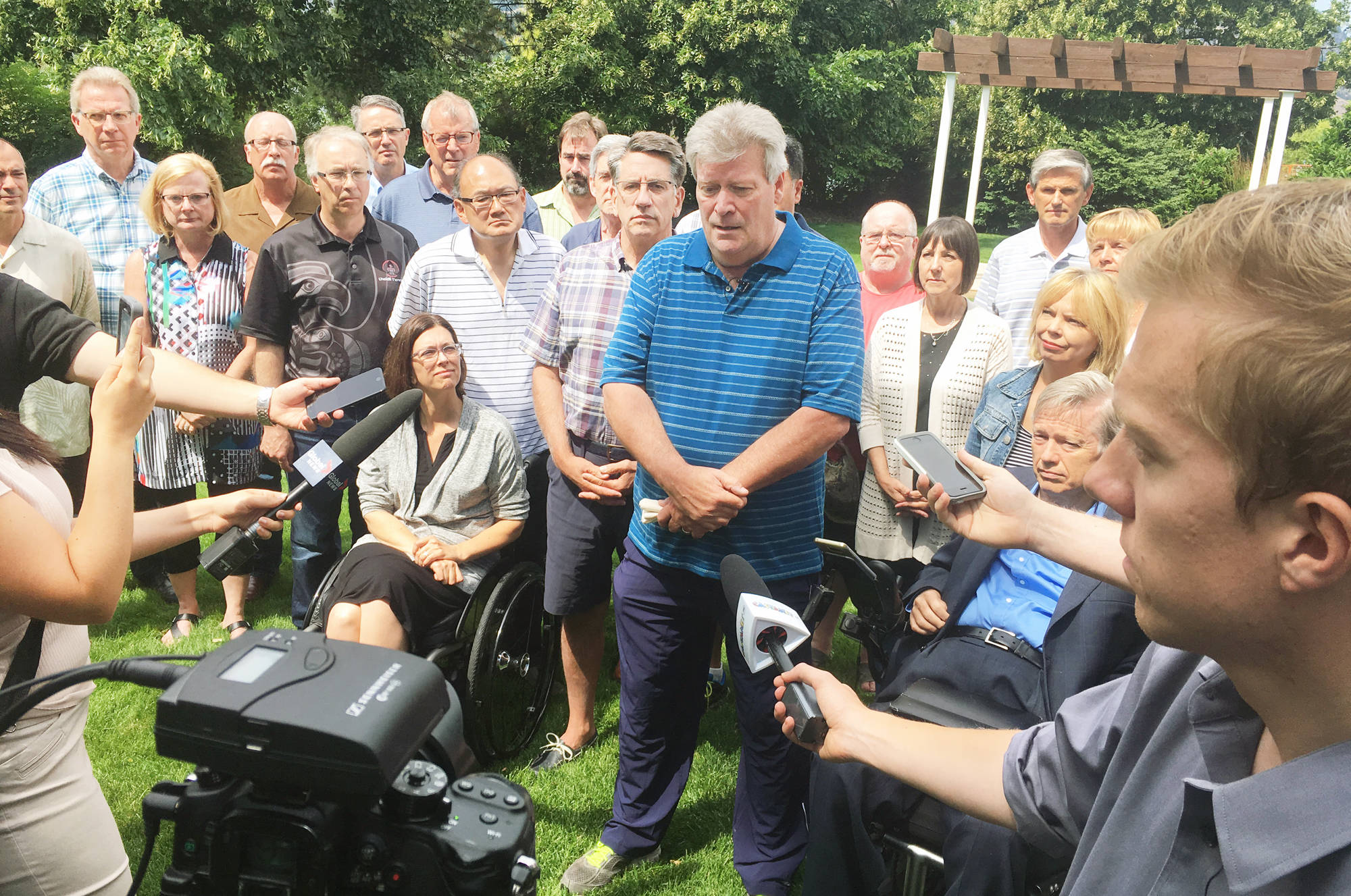 Interim Liberal Party Leader Rich Coleman, surrounded by caucus members, talks to the media outside the Penticton Lakeside Resort Friday afternoon following the announcement former Premier Christy Clark was stepping down as party leader as of Aug. 4. Mark Brett/Western News