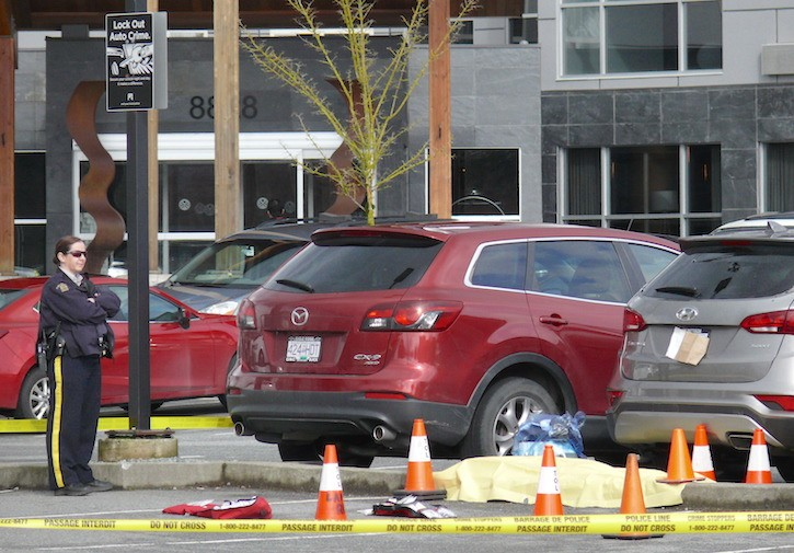An RCMP officer at the scene of a fatal shooting in a Langley hotel parking lot.