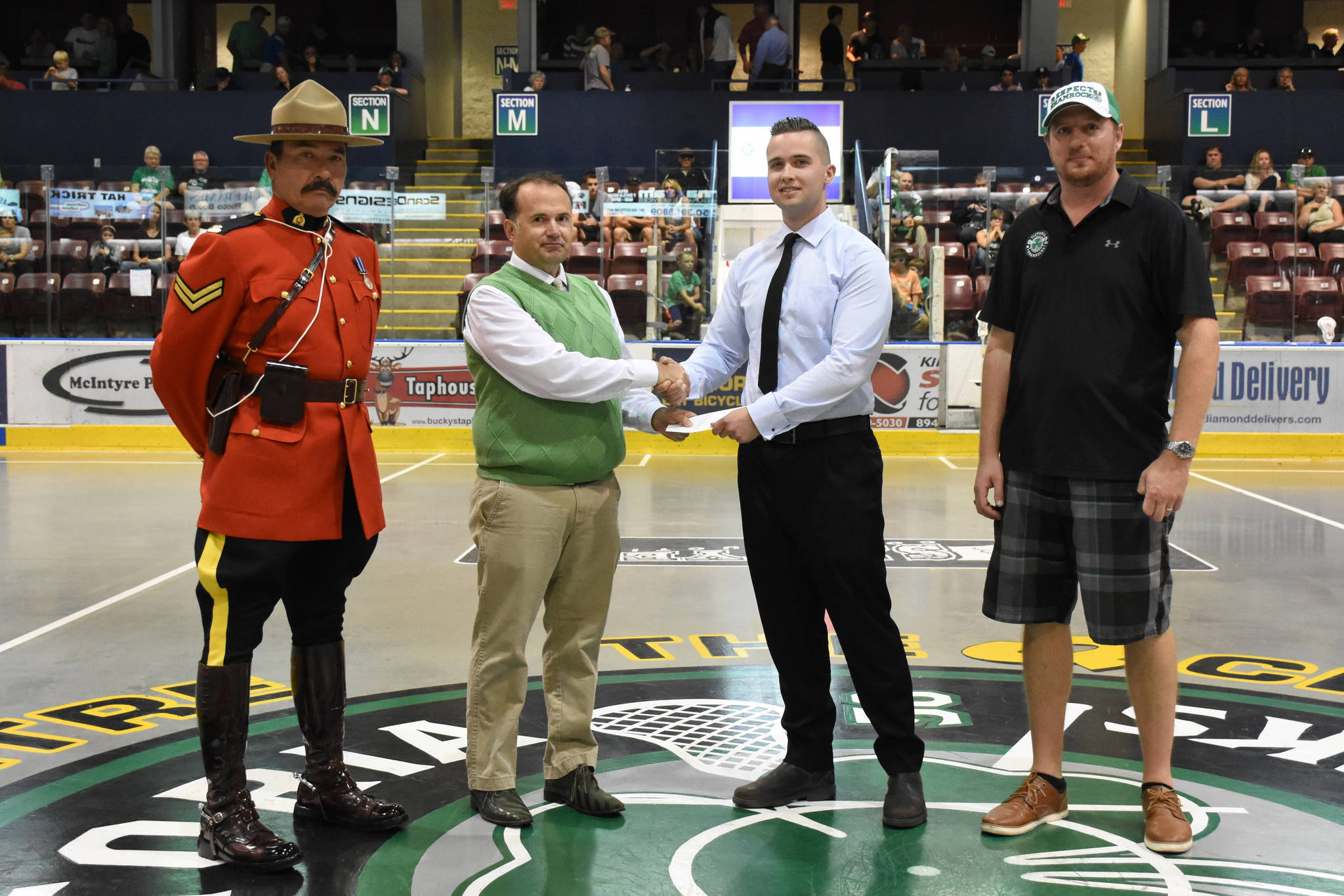 Tanner Stevenson, centre right, is presented with the inaugural Const. Sarah Beckett Memorial Scholarship by Colin Plant (centre left), Victoria Shamrocks operations manager Jason Sperling (far right), and Cpl. Heinz Krauss (far left) on Aug. 13. (Photo by Jen Powley/Victoria Shamrocks)