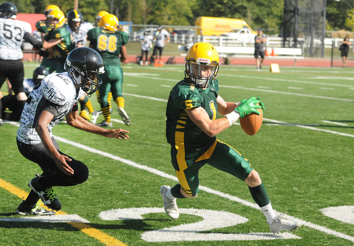 Langley Saints ball carrier Landon McArthur looked to turn the corner while being pursued by a Frank Hurt Hornets tackler in high school AA varsity football action Friday afternoon at McLeod Stadium. The Saints defeated the Hornets 44-7 in the exhibition match-up. Troy Landreville Langley Times