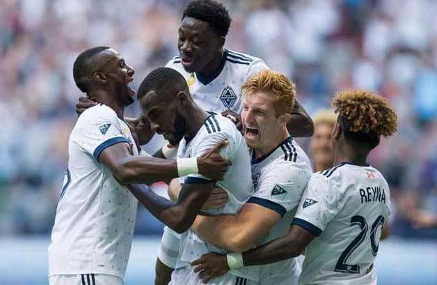 Vancouver Whitecaps' Bernie Ibini, from left, Tony Tchani, Alphonso Davies, Tim Parker and Yordy Reyna celebrate Tchani's tying goal against the Columbus Crew during the second half of an MLS soccer game in Vancouver on September 16, 2017. (Darryl Dyck/Canadian Press)