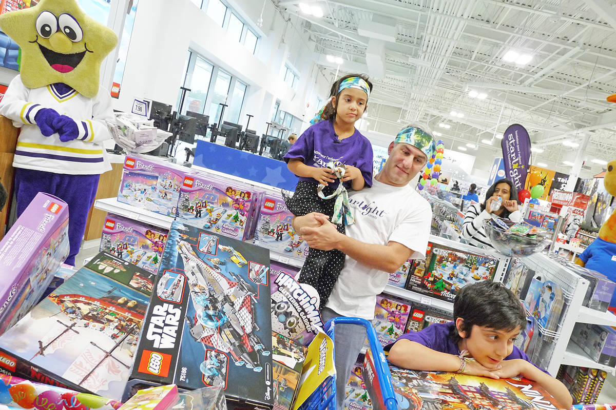 "Raffi Mahseredjian lifts up daughter Talia so she can get a better look at the toys the family collected during a three-minute dash through the Langley Toys ""R"" Us store. Dan Ferguson Langley Times"