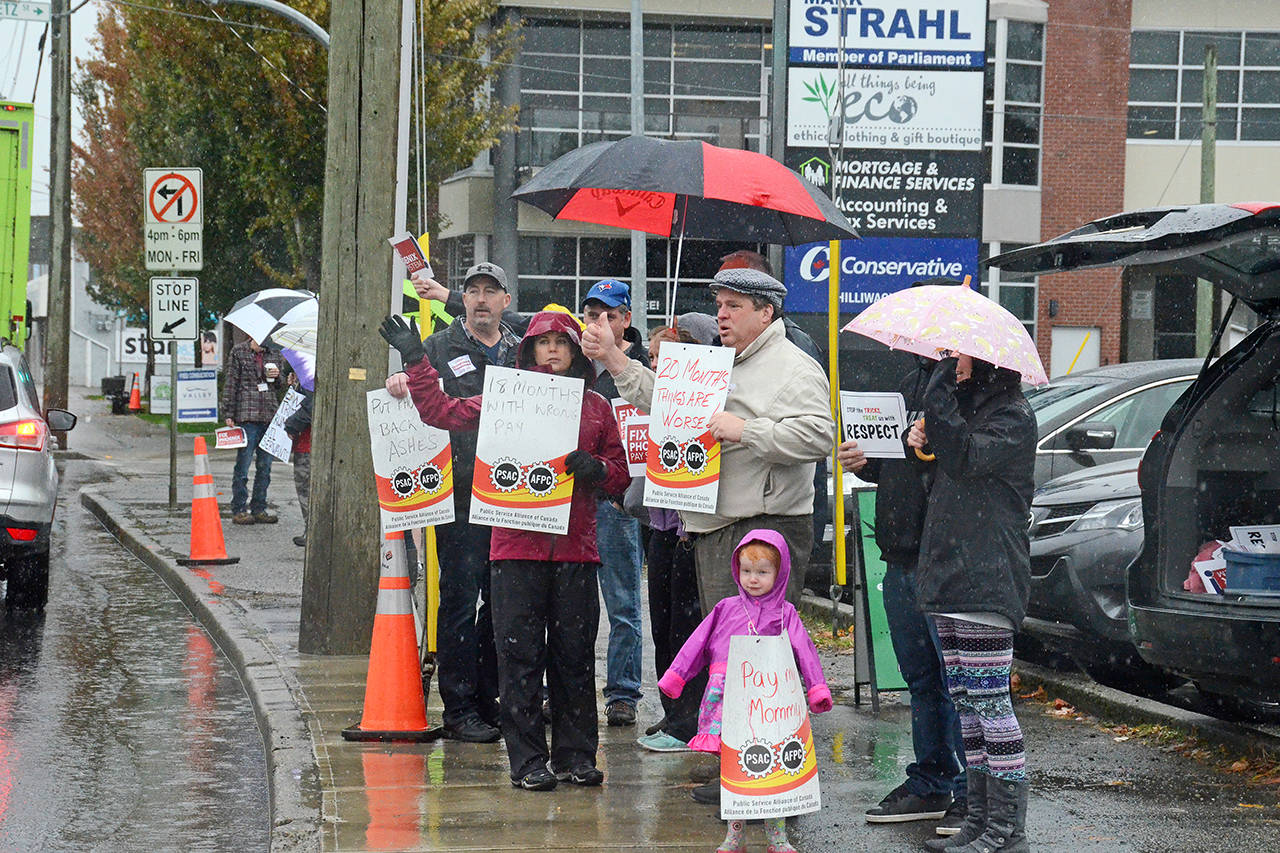 Federal employees frustrated with the Phoenix pay system rally in front of Chilliwack-Hope MP Mark Strahl's office Wednesday afternoon. (Paul Henderson/ The Progress)