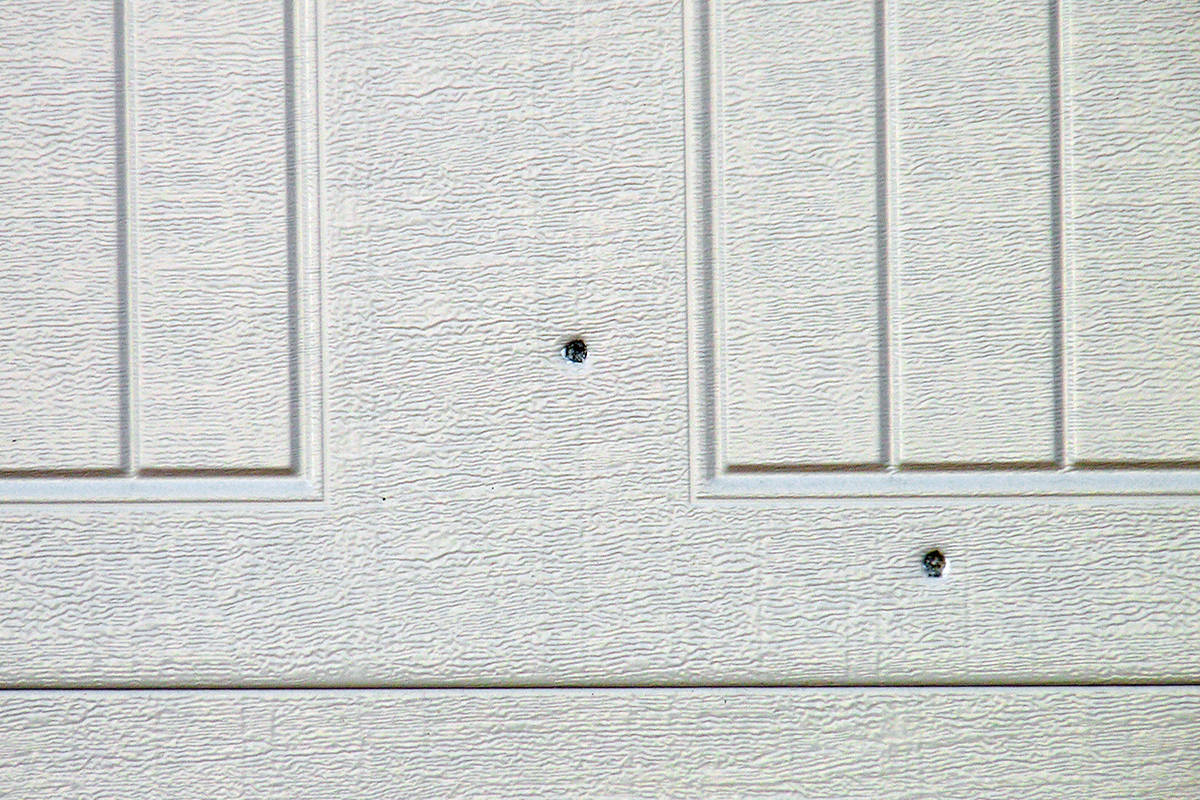 What appeared to be bullet holes could be observed in the garage door of the targeted house. Dan Ferguson Langley Times