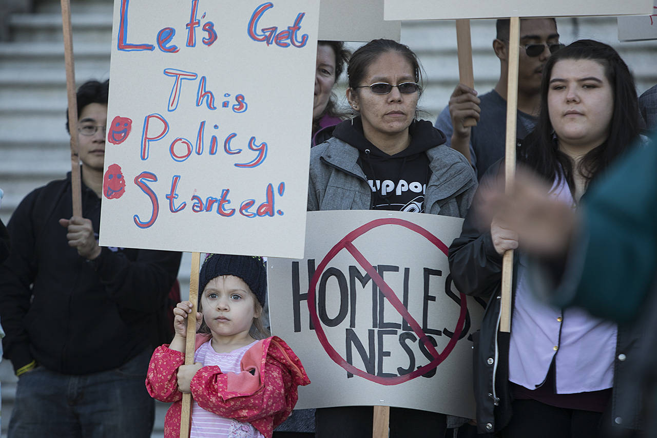 A young girl holds up a sign as hundreds of people, many youth who have aged out of foster care, rallied at the steps of the BC Legislature to ask for better support for youth aging out of care. (Arnold Lim/Black Press)
