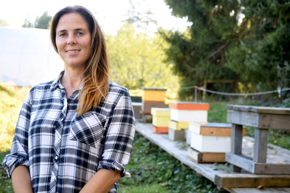 Melanie MacInnes stands in front of several beehives that were introduced to the MacInnes Farm. Next year, they plan to expand their hives to 60. Miranda Gathercole Langley Times.