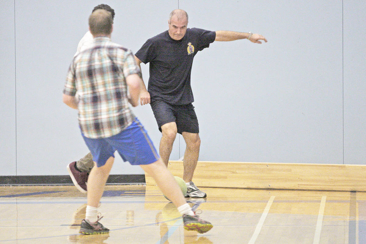 RCMP Constable Mo Beyhaghi (in black) competes with students for the soccer ball. Dan Ferguson photo