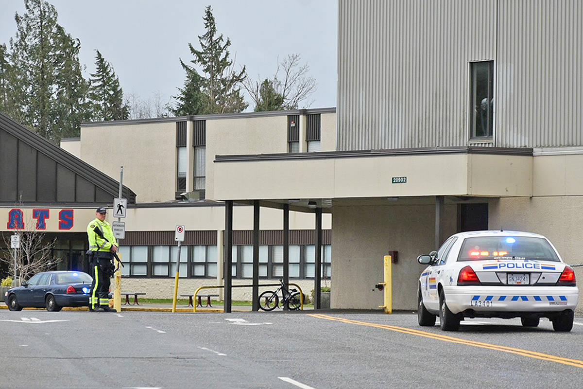 An armed police officer stands outside Brookswood Secondary School. A lockdown was ordered in response to a report of a suspicious male, possibly armed. Miranda Gathercole Langley Times