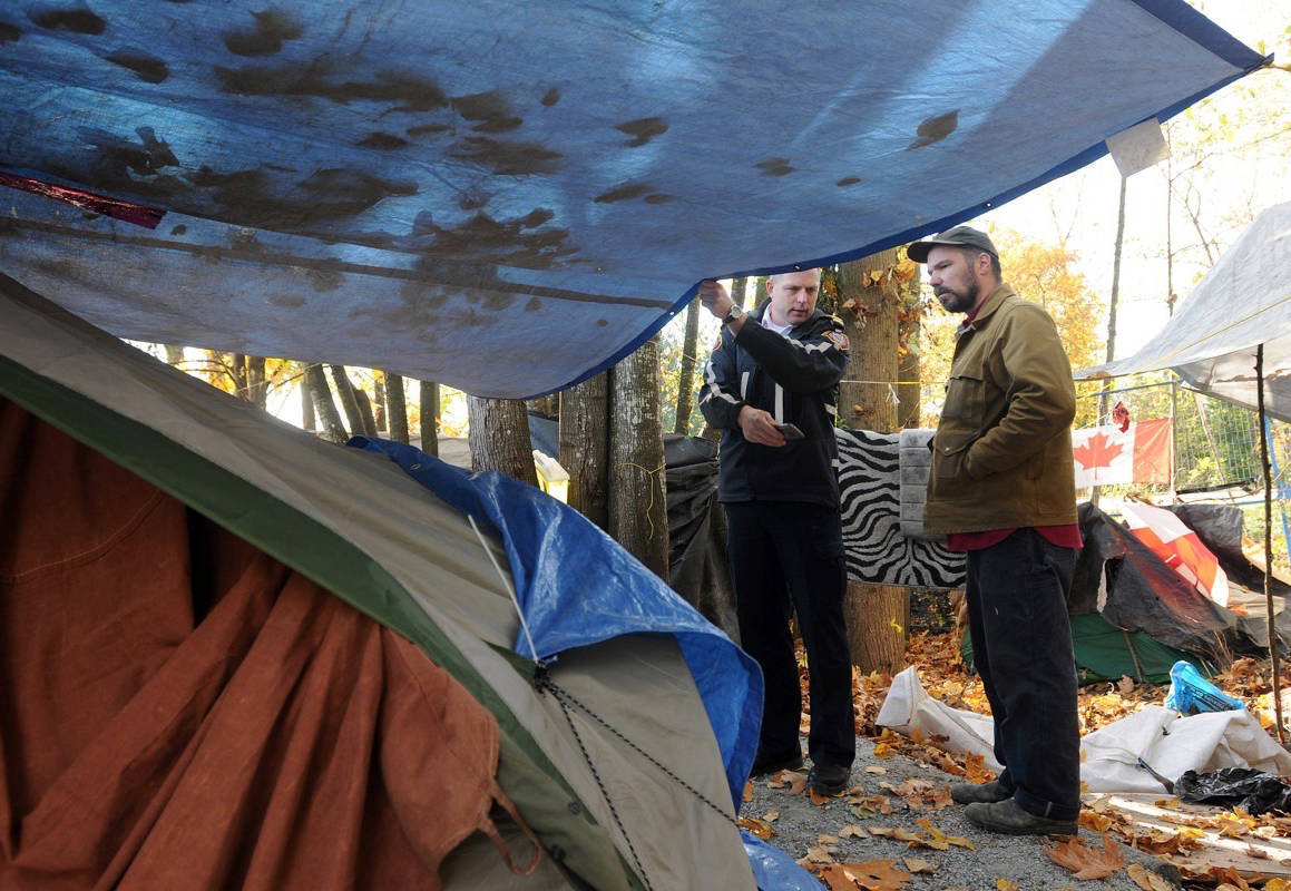 The Maple Ridge Fire Department along with people from the City of Maple Ridge and the Ridge Meadows RCMP do a walk-through of Anita Place Tent City with Ivan Drury. (News files)