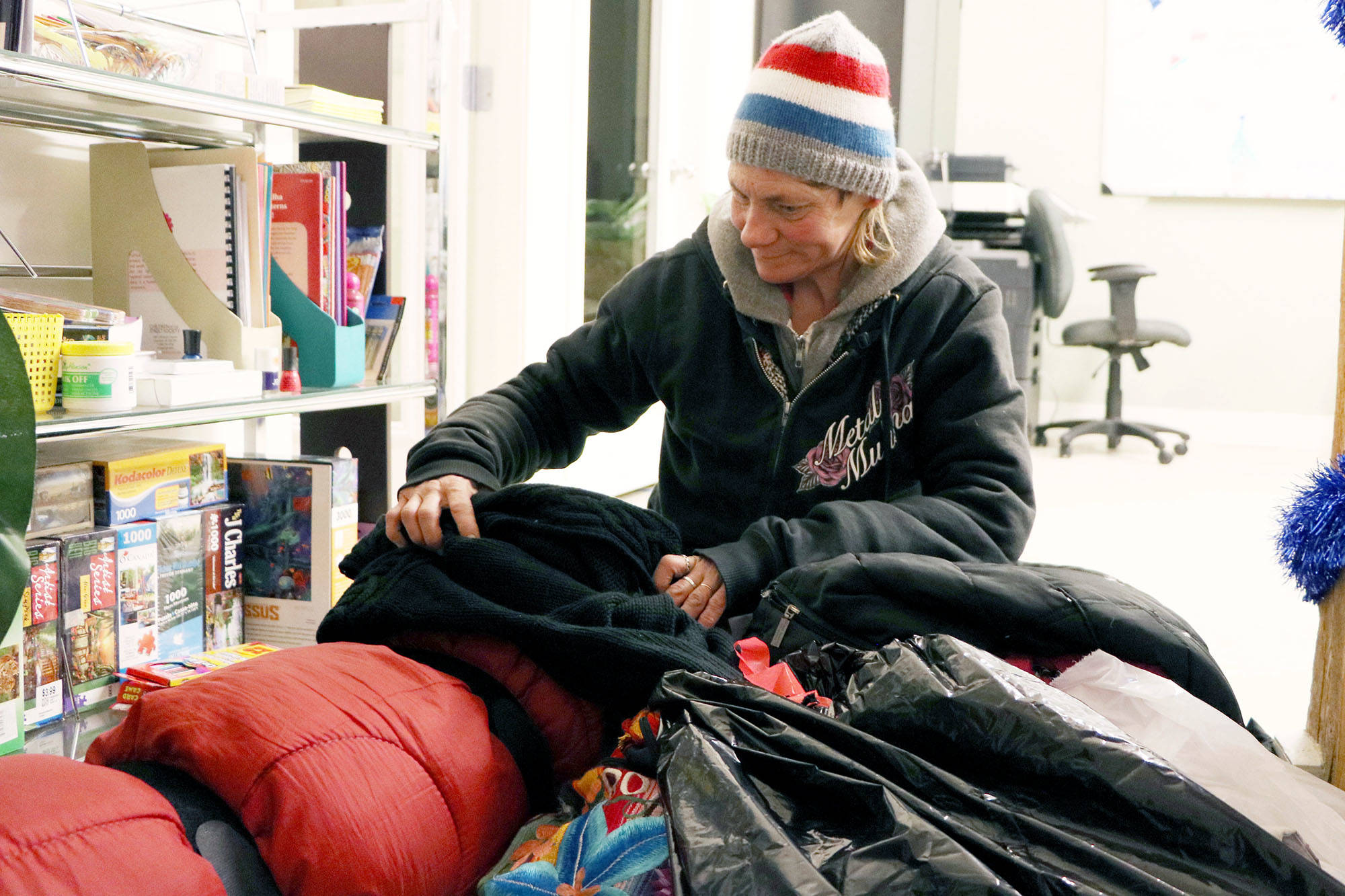 Kathy Schuster, 45, sorts some of her belongings in the South Okanagan Women In Need Society's SAFExst space at an unspecified location, where she gets a bit of warmth and can stock up on some basic supplies. For Schuster, a loss of supplies is a serious personal security matter.                                Dustin Godfrey/Western News