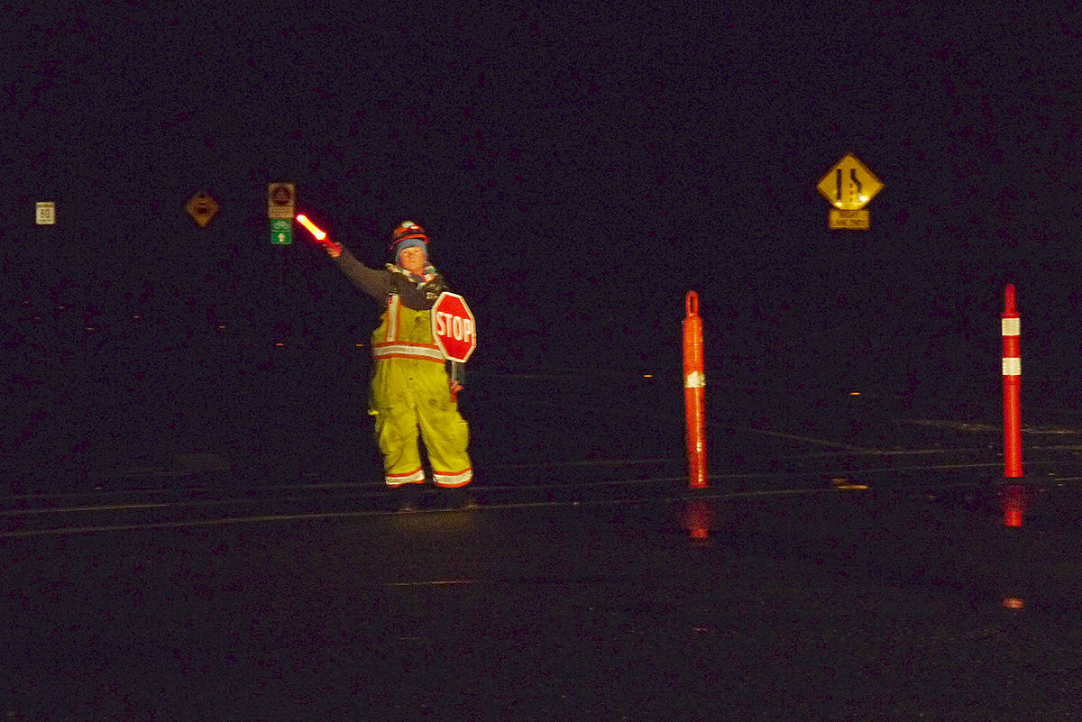 A flagger redirects traffic away from Fraser Highway. Downed power lines, the result of a winter storm, forced an all-day road closure. Dan Ferguson Langley Times.