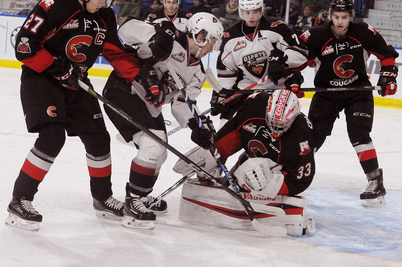 Vancouver Giants poke away at the puck as Isaiah DiLaura looks to cover it in WHL action at the Langley Events Centre on Saturday. Troy Landreville Black Press