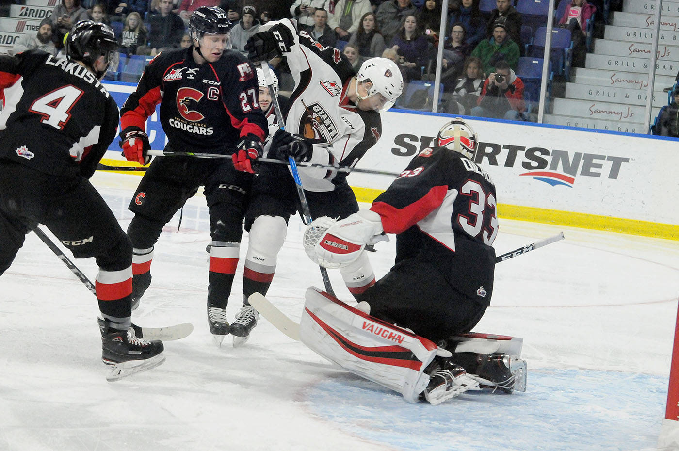 Prince George Cougars defenceman Dennis Cholowski checksVancouver Giants left winger Owen Hardy in front of the Cougars goal during Saturday's WHL match-up at the Langley Events Centre. Troy Landreville Black Press