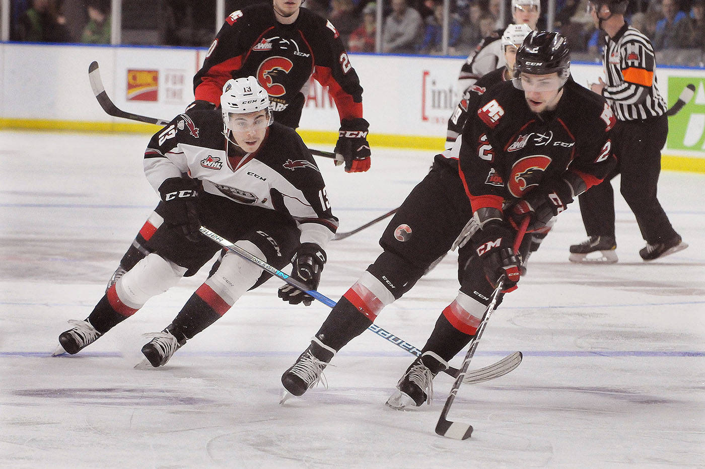 Prince George Cougars defenceman Cole Moberg looks to evade the forechecking of Vancouver Giants centre Tyler Popowich in the first period of Saturday's WHL game at the Langley Events Centre. Troy Landreville Black Press