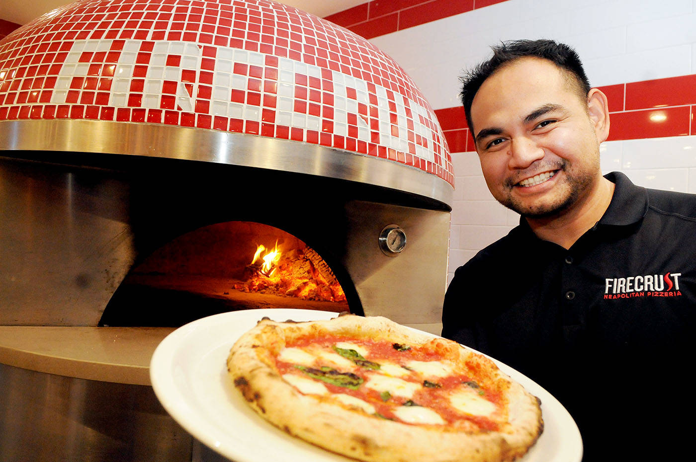 Randy Rivera held a pizza during Friday's invitation-only celebration of Firecrest Custom Salads and Pizzas on the Langley Bypass. Troy Landreville Langley Times