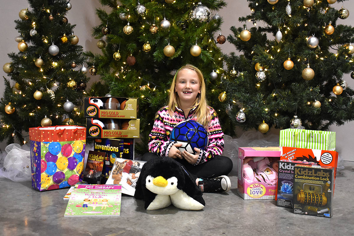Alex McGowan, 8, sits surrounded by the presents she donated to the Cloverdale Christmas Hamper. (Sam Anderson)
