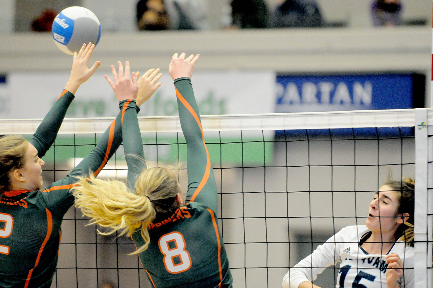 Seaquam Seahawks' Brynn Pasin sent the ball over past the outstreched fingertips of a pair of Earl Marriott Mariners players during Friday's 4A girls quarter-finals, won by Earl Marriott. The match was part of the Big Kahuna BC Volleyball Championships that wrap up Saturday with the gold medal games at the Langley Events Centre. Troy Landreville Black Press